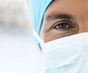 Young Male Doctor Wearing Protective Headgear and Face Mask --- Image by © Royalty-Free/Corbis